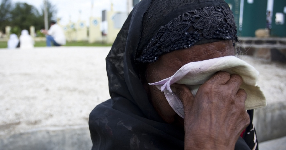 A woman weeps at Ule Lheu mass grave in Banda Aceh, Indonesia, as she prays for her family five years after they died in the 2004 tsunami. (Fauzan Ijazah/GlobalPost)</p>