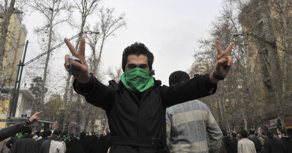 An Iranian protester with his face covered by the opposition-colored green mask flashes the victory sign as he holds stones during clashes in central Tehran Dec. 27, 2009.</p>