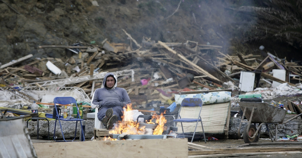 A resident warms himself up with a fire amid debris left by the waves generated by a major earthquake, in the surfing community of Pichilemu, Chile, March 1, 2010.</p>
