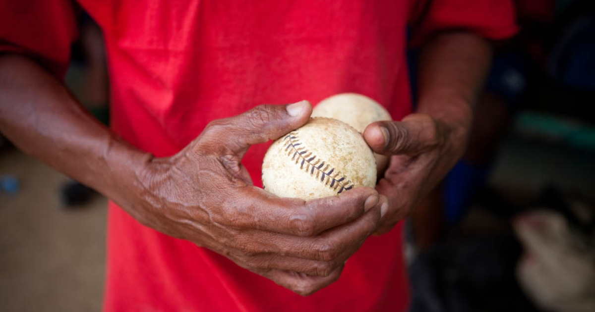 Coach Hector Ramirez holds two baseballs during practice for the Warriors baseball team at the municipal stadium on Thursday, February 25, 2010 in San Antonio de Guerra, Dominican Republic.</p>