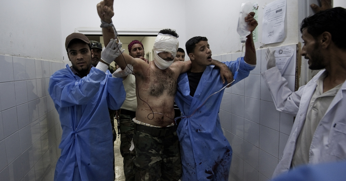 A Libyan rebel wounded during the battle for the control of the Brega flashes a victory sign as he is rushed into the emergency room at the general hospital in Ajdabiya, on July 17, 2011.</p>