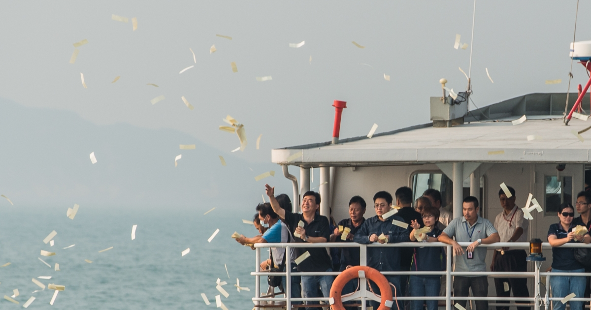 Mourners throw paper money into the sea during a ceremony held for the victims of the victims of a ferry collision off Lamma Island in Hong Kong on October 4, 2012.</p>