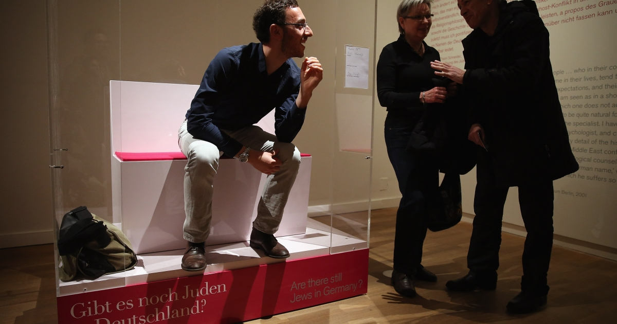 Bill Glucroft, an American Jew living in Berlin, chats with visitors from his box in the 'live exhibit' portion of the exhibition