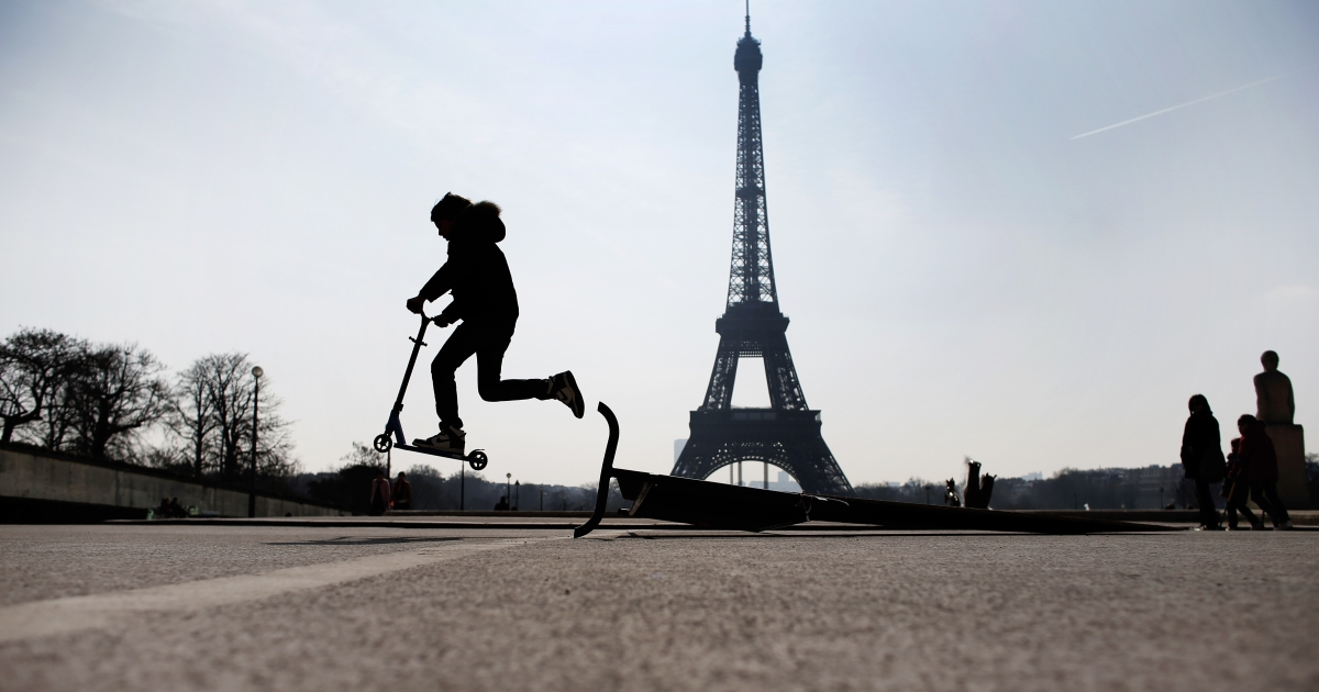 A child rides a scooter on the Trocadero square, in front of the Eiffel tower, on April 7, 2013.</p>