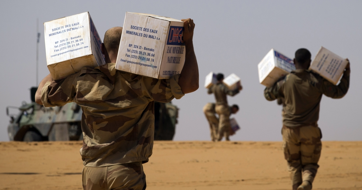 French soldiers from the 126th Regiment Infantery carry boxes containing water bottles on April 8, 2013 some 105 kilometers North of Gao.</p>
