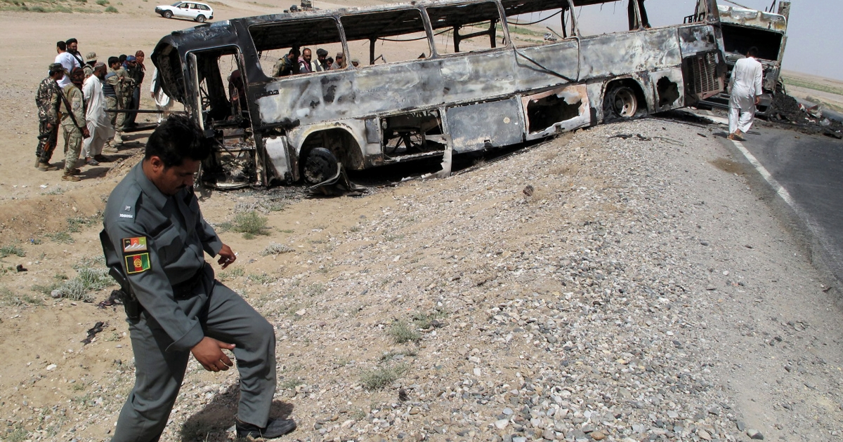 Traffic police officials inspect the site where a passenger bus collided with a fuel tanker truck in Kandahar province on April 26, 2013. The crash was blamed a Taliban insurgent attack.</p>