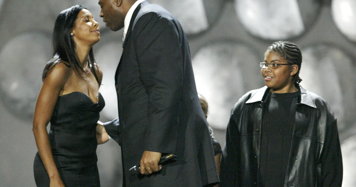Los Angeles Lakers player Earvin 'Magic' Johnson greets his wife Cookie as his son Earvin III watches onstage at 'The Rewarding Life of Earvin (Magic) Johnson