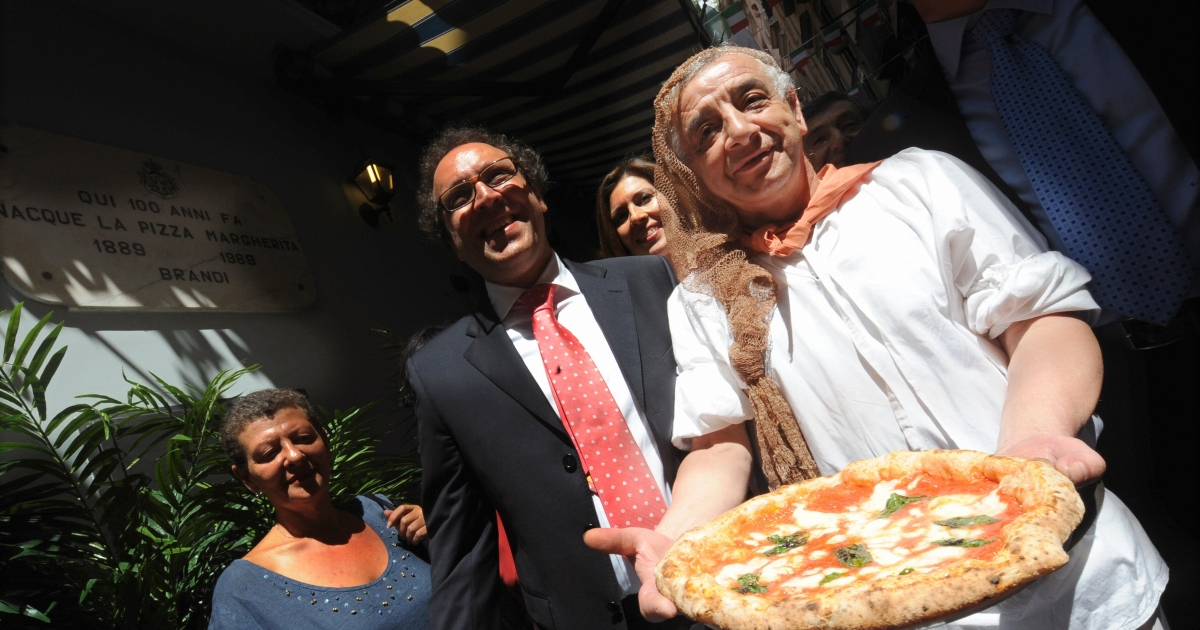 A pizzaiolo of the Brandi restaurant holds a pizza named after Queen Margherita of Savoy during a ceremony to celebrate the 120th anniversary of the pizza Margherita on June 11, 2009 in Naples.</p>