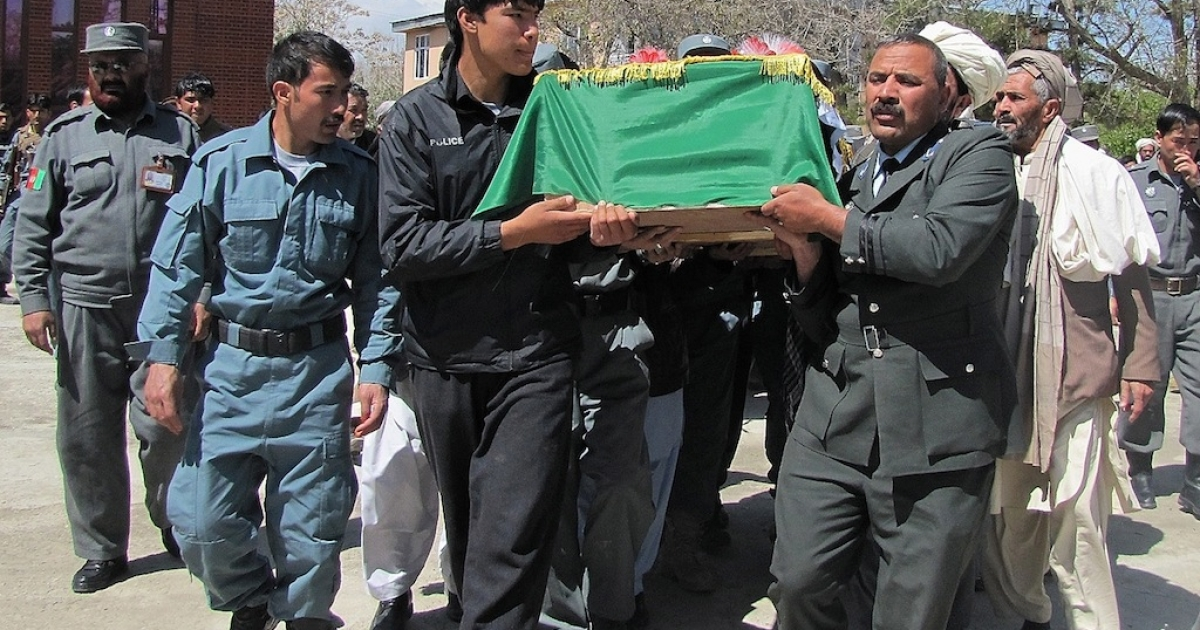 Afghan men carry the coffins of police officers who were killed in a roadside bomb ambush in Ghani province on April 28, 2013.</p>