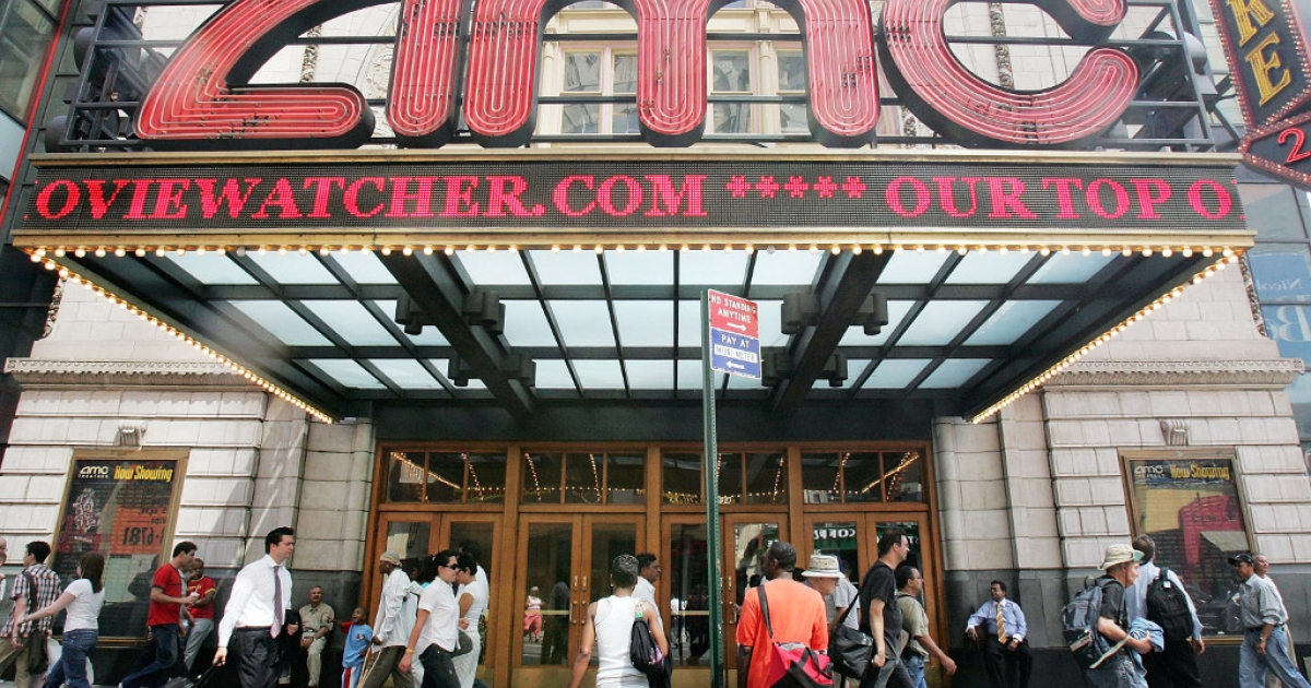 Pedestrians pass an AMC movie theater in Times Square June 21, 2005 in New York City.</p>