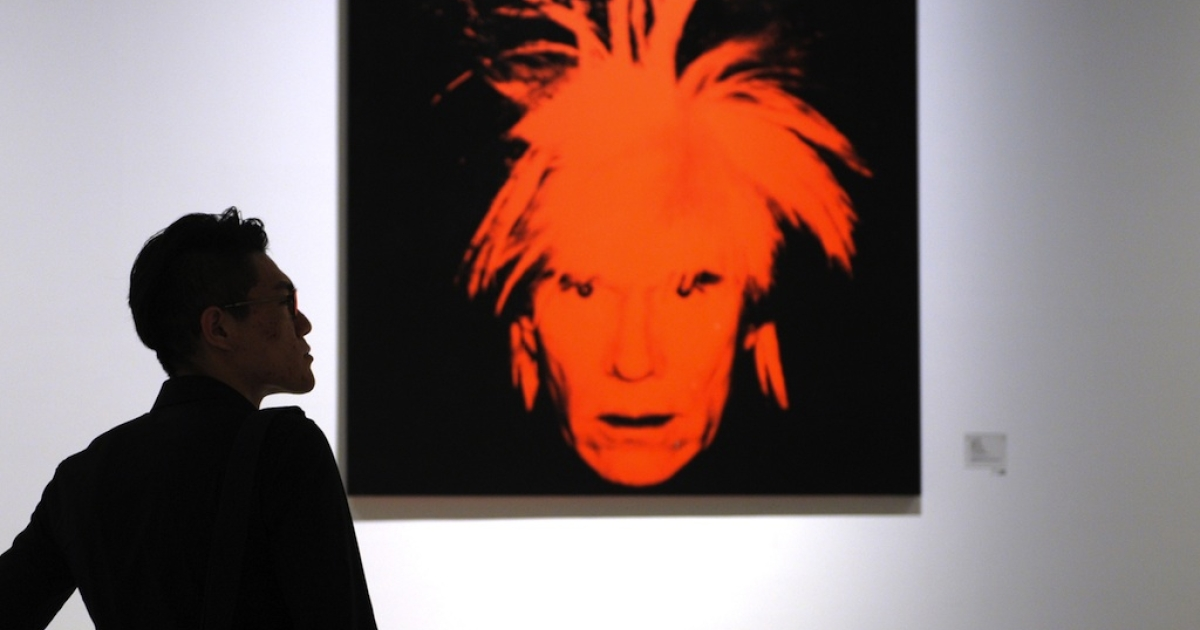 A visitor looks at a retrospective of works by American pop artist Andy Warhol at the Shanghai Power Station of Art museum on April 28, 2013.</p>