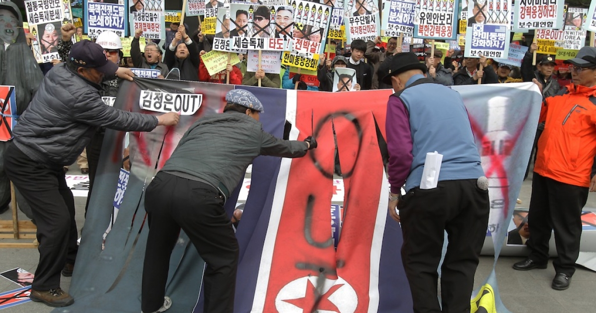 South Korean protesters deface a North Korean flag during a rally against North Korea on April 15, 2013 in Seoul, South Korea.</p>
