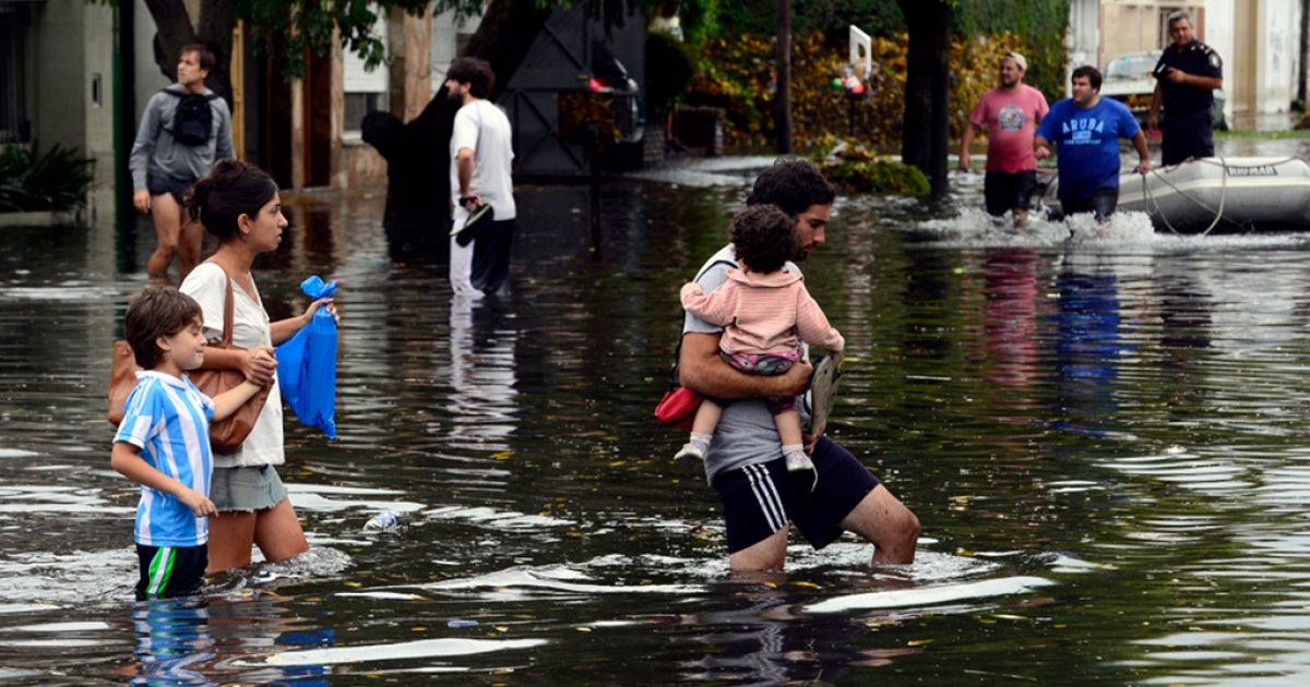 People wade through flooded streets as the water starts subsiding in La Plata, located 63 km south of Buenos Aires, on Apr. 3, 2013 after a powerful storm pummeled the Argentine capital overnight from Tuesday to Wednesday.</p>