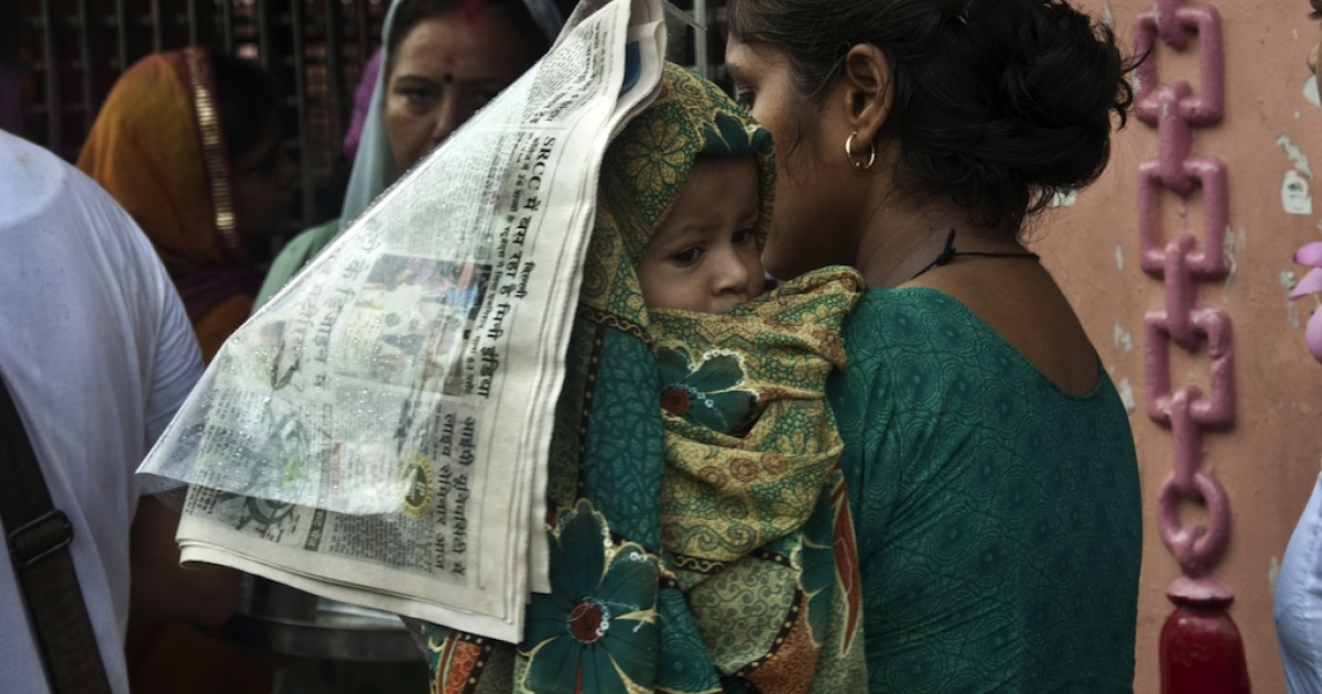 An Indian woman covers her baby with a newspaper as she waits in line to offer prayers at the Gauri Shankar Temple in New Delhi on July 9, 2012.</p>