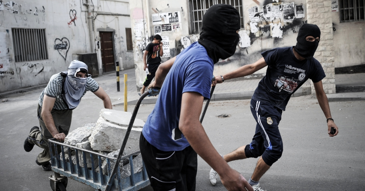 Bahraini protesters use a trolley to carry bricks during clashes with riot police following a protest against the Formula One Grand Prix on April 19, 2013 in the village of Sanabis, west of Manama.</p>