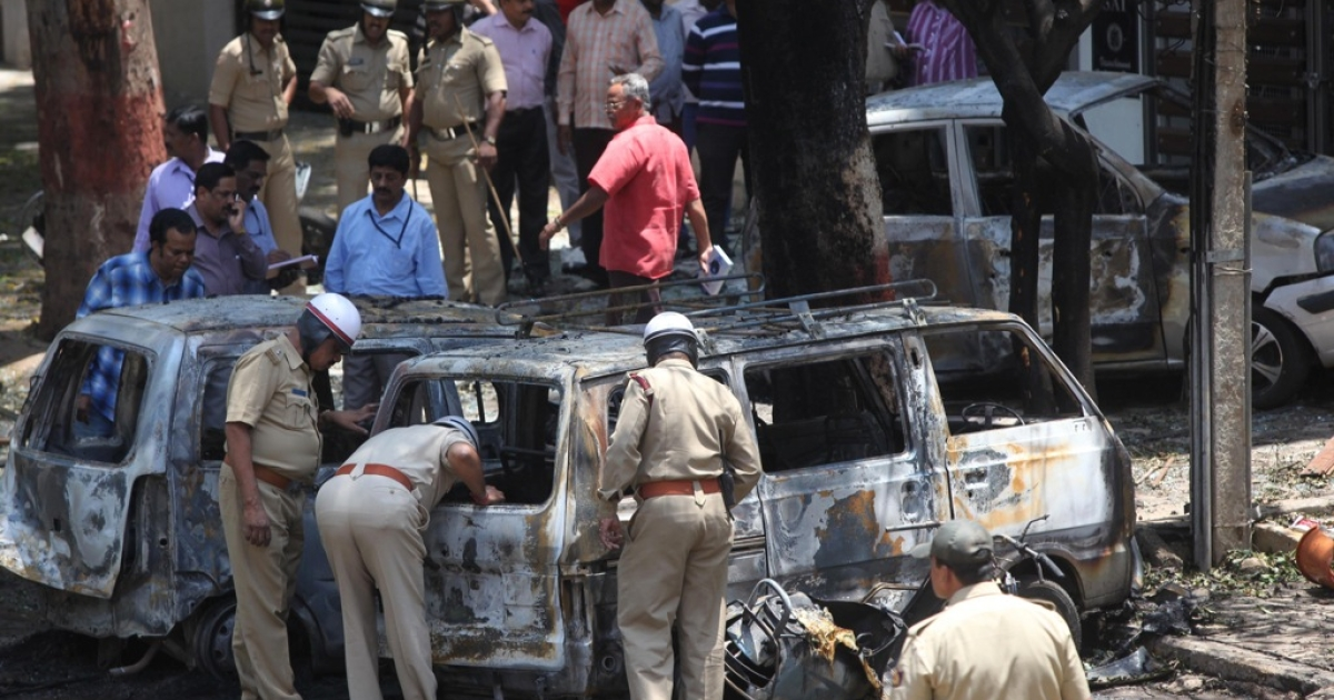 Indian police search for evidence inside burned vehicles following a blast near the Bharatiya Janata Party (BJP) office in Bangalore on April 17, 2013. Police in the southern city of Bangalore said Wednesday they were investigating a minor blast outside the office of a political party which injured 12 people.</p>