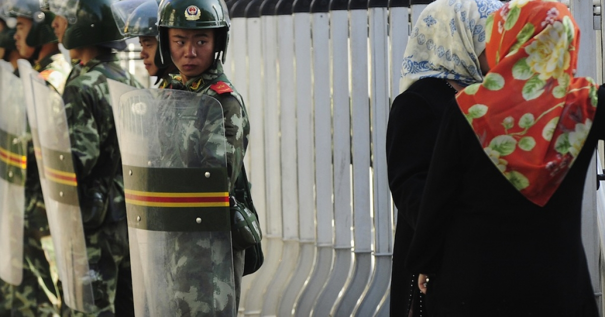 An ethnic Uigur women look through a security fence to the Grand Bazaar which remains closed as Chinese soldiers look on in Urumqi, in China's farwest Xinjiang region on July 9, 2009.</p>