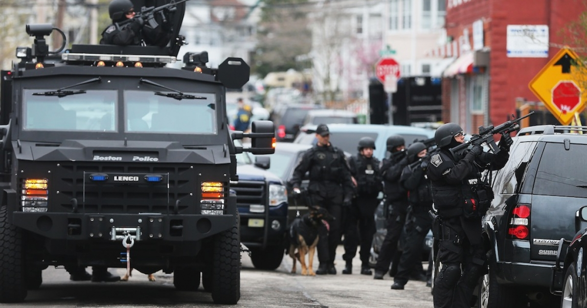 SWAT team members aim their guns as they search for one remaining suspect at an apartment building on April 19, 2013 in Watertown, Massachusetts. Earlier, a Massachusetts Institute of Technology campus police officer was shot and killed at the school's campus in Cambridge. A short time later, police reported exchanging gunfire with alleged carjackers in Watertown, a city near Cambridge. According to reports, one suspect has been killed during a car chase and the police are seeking another — believed to be the same person (known as Suspect Two) wanted in connection with the deadly bombing at the Boston Marathon earlier this week. Police have confirmed that the dead assailant is Suspect One from the recently released marathon bombing photographs.</p>