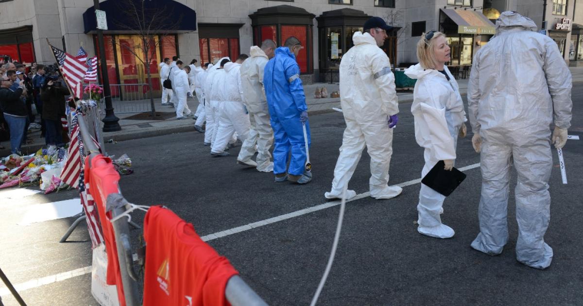 FBI crime scene investigators sweep up Boylston Street just past Berkeley Street towards the scene of the bombing looking for evidence April 17, 2013 in Boston, Massachusetts.</p>