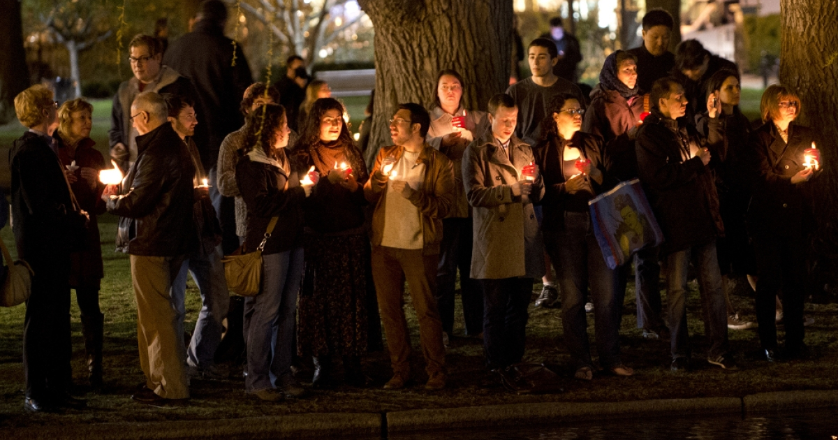 Mourners gather on the edge of the pond in the Boston Public Gardens for a candlelight vigil April 16, 2013 in Boston. A few hundred people gathered to remember the victims of the bombs which exploded during the running of the Boston Marathon.</p>