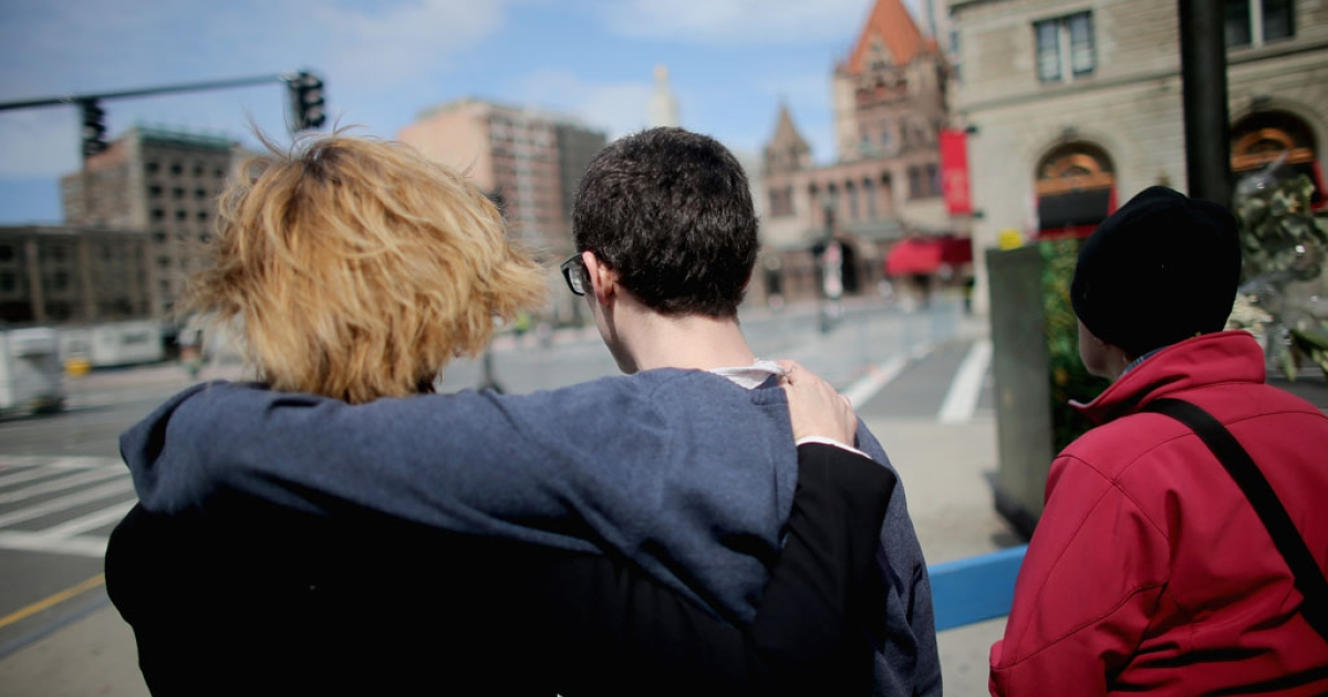 People embrace before a moment of silence honoring the Boston Marathon bombing victims in Copley Square, near the bombing sites, on April 22, 2013 in Boston, Massachusetts.</p>