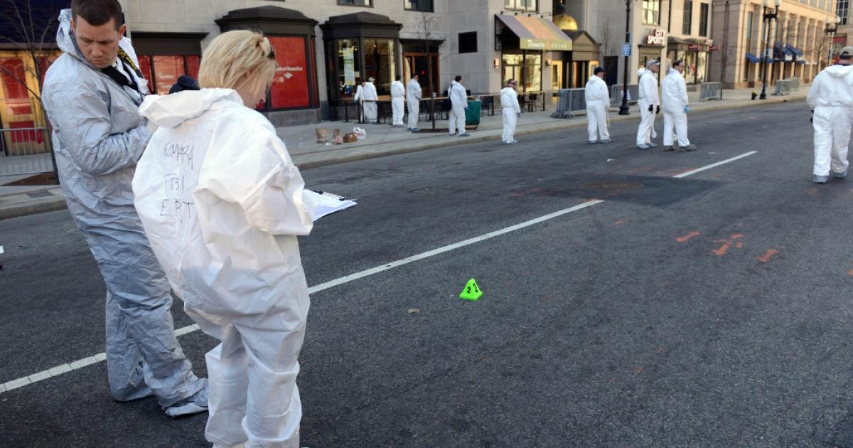 FBI crime scene investigators stand near an evidence marker on Boylston Street just past Berkeley Street as they sweep up towards the bomb scene of the Boston Marathon April 17, 2013 in Boston, Massachusetts.</p>