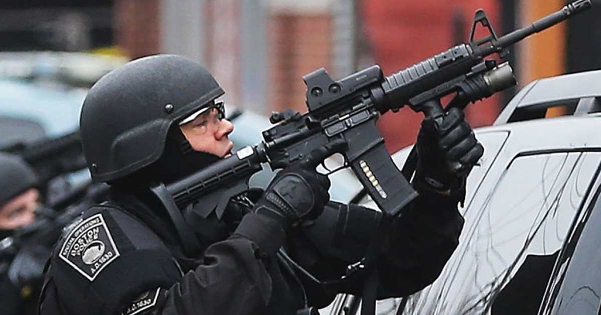A Boston SWAT team member takes up as posistion during the search for 19-year-old bombing suspect Dzhokhar A. Tsarnaev on April 19, 2013 in Watertown, Massachusetts.</p>