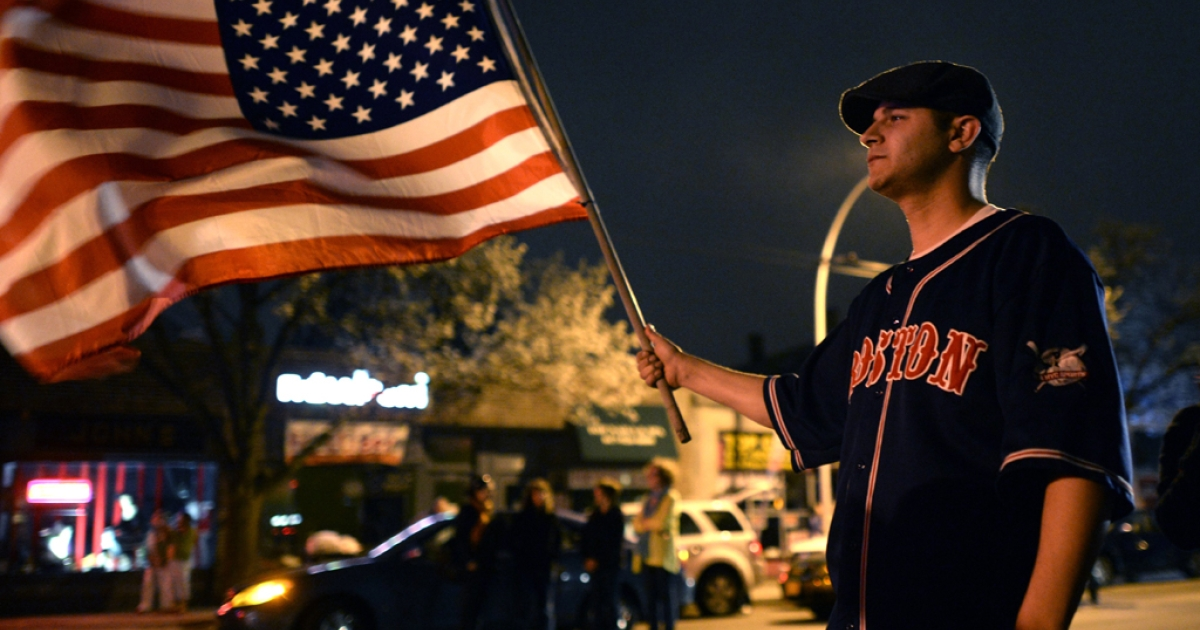 A man waves the US flag after the capture of the second of two suspects wanted in the Boston Marathon bombings April 19, 2013 in Watertown, Massachusetts.</p>