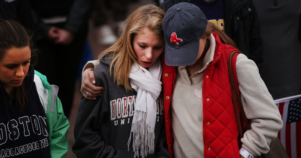 Two mourners hug during a vigil for victims of the Boston Marathon bombings at Boston Commons on April 16, 2013.</p>