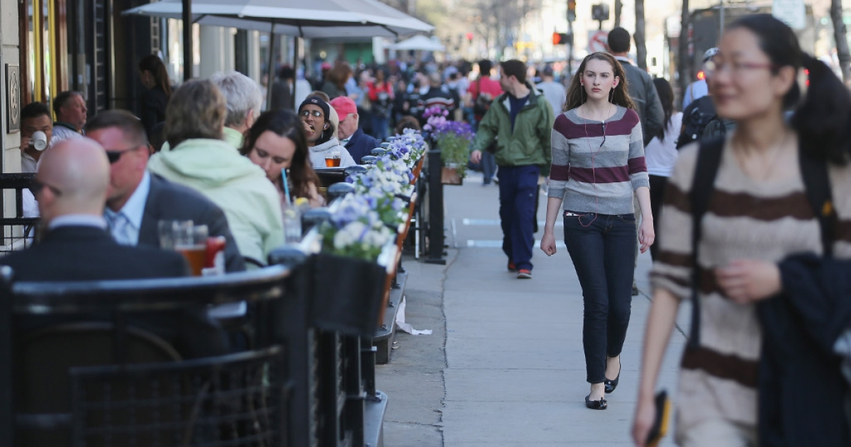 People walk and dine along Boylston Street near the site of the Boston Marathon bombings on April 24, 2013 in Boston, Massachusetts. Boylston Street, the site of both bombings, finally fully reopened to the public Wednesday.</p>