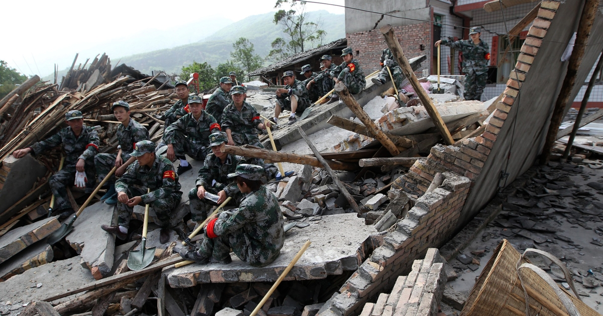 Rescuers sit on ruins of a house in Longmen township, an area very close to the epicenter of an earthquake that hit the city of Ya'an, southwest China's Sichuan province on April 20, 2013.</p>