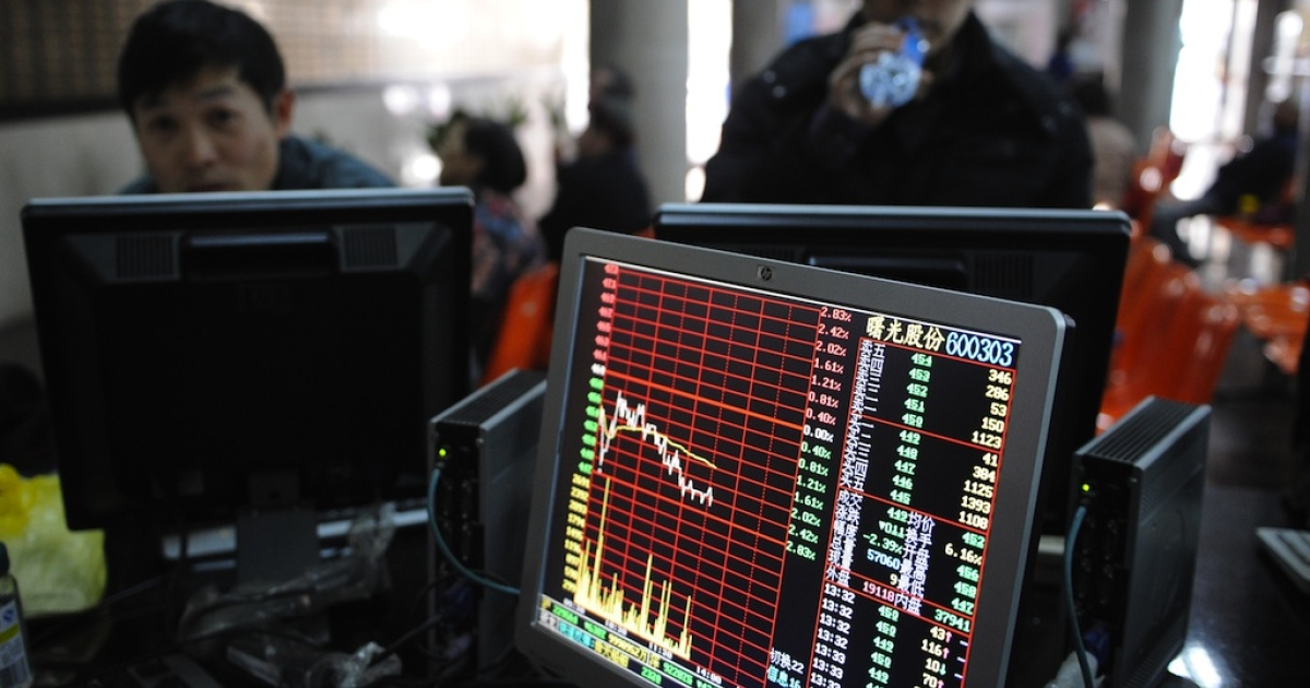 Investors look at stock prices on a screen at a securities exchange in Shanghai on March 4, 2013.</p>