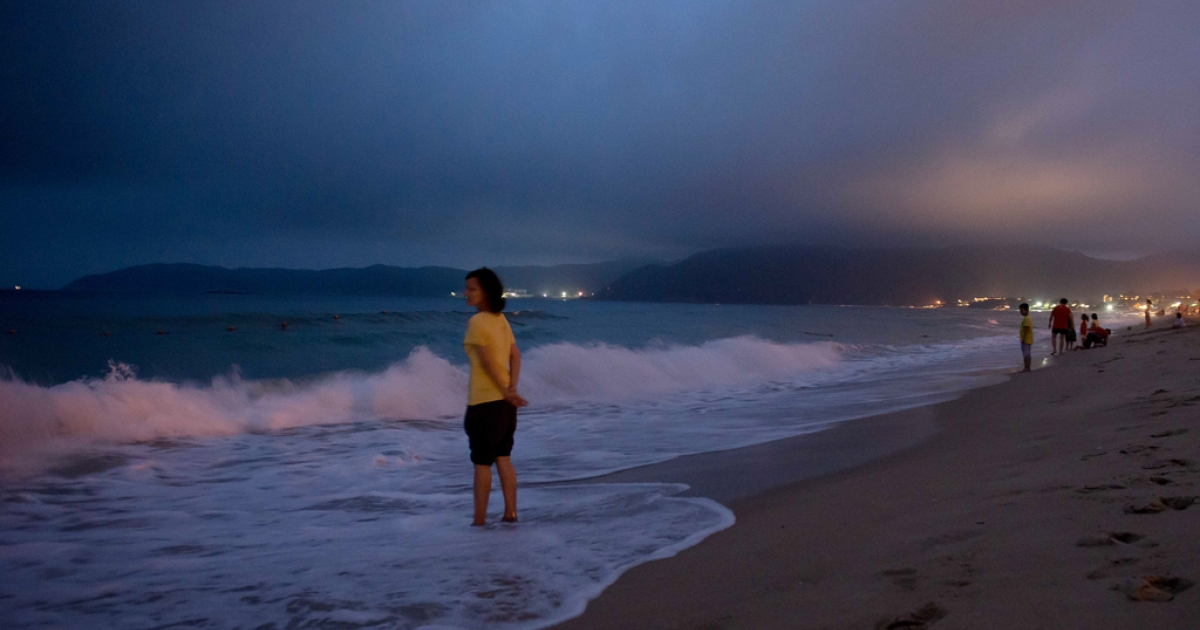 A woman stands in the sea at a beach in the Yalong Bay area of Sanya, on the southern Chinese island of Hainan on Apr. 4, 2013.</p>