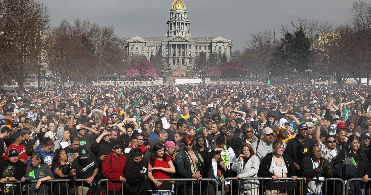 Marijuana smoke rises from a crowd at a pro-pot '4/20' celebration in front of the state capitol building in Denver, Colo., on April 20, 2010.</p>