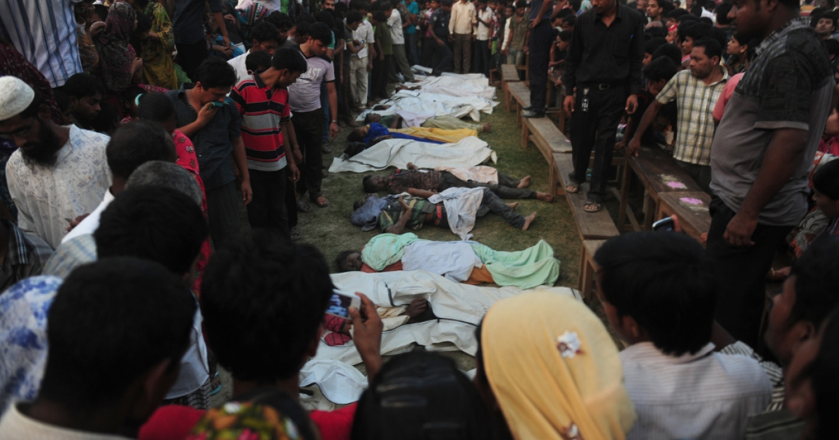 Bangladeshi relatives look at dead bodies after a building collapse in Savar, on the outskirts of Dhaka, on April 24, 2013.</p>