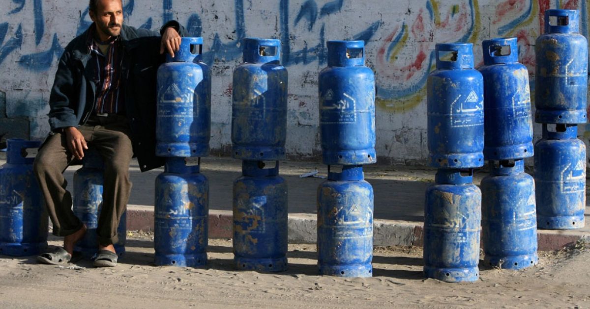 A Palestinian man sits with cylinders of cooking gas, smuggled into the Gaza Strip from Egypt through a tunnel, that he is selling on a street in Gaza city.</p>