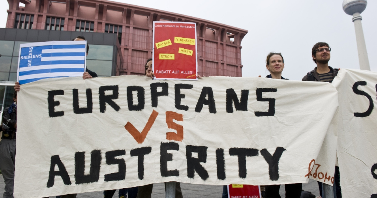 Greek activists display a banner reading 'Europeans vs austerity' as they stage a protest opposite the venue of a meeting of the Federation of German Industry in Berlin September 27, 2011.</p>