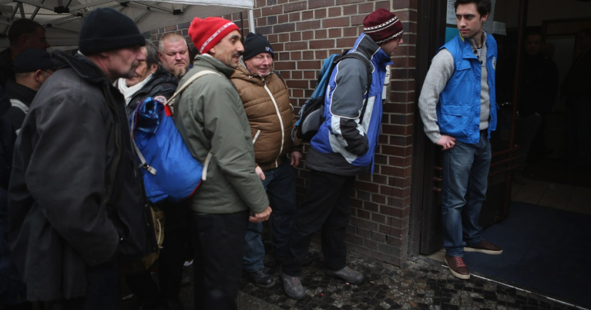 Visitors, mostly homeless men, wait outside the Bahnhofsmission Protestant charity facility for a free lunch as theology student and volunteer Markus (R) prepares to let them in at Zoo train station on February 20, 2013 in Berlin, Germany. Both poverty and pensions that have not kept up with the rising cost of living will be contested topics in federal elections scheduled later for this year.</p>