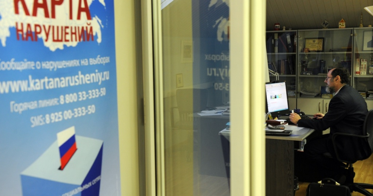 A picture taken through a glass window shows a staffer of Russia's leading independent election watchdog Golos working at the monitoring body's office in Moscow on December 2, 2011. Golos was fined for refusing to comply with Russia's new law on NGOs on April 26, 2013.</p>