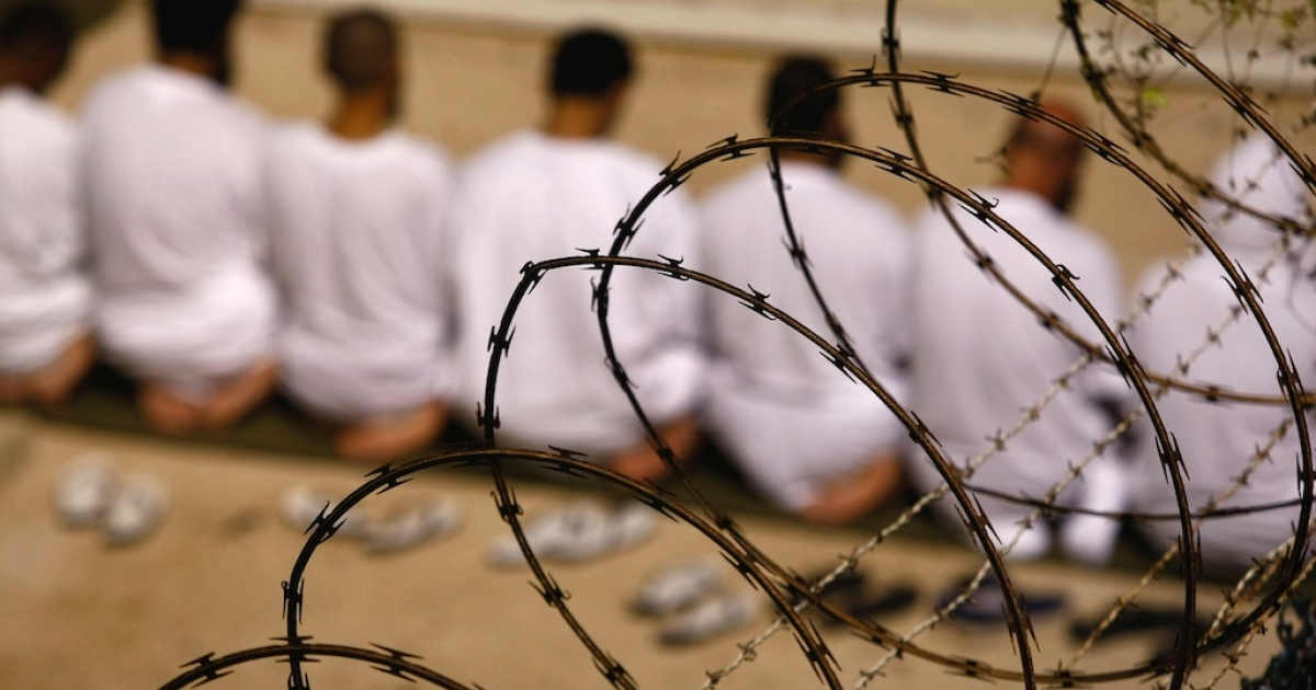 A group of detainees kneels during early morning prayer in the camp at the US military prison for