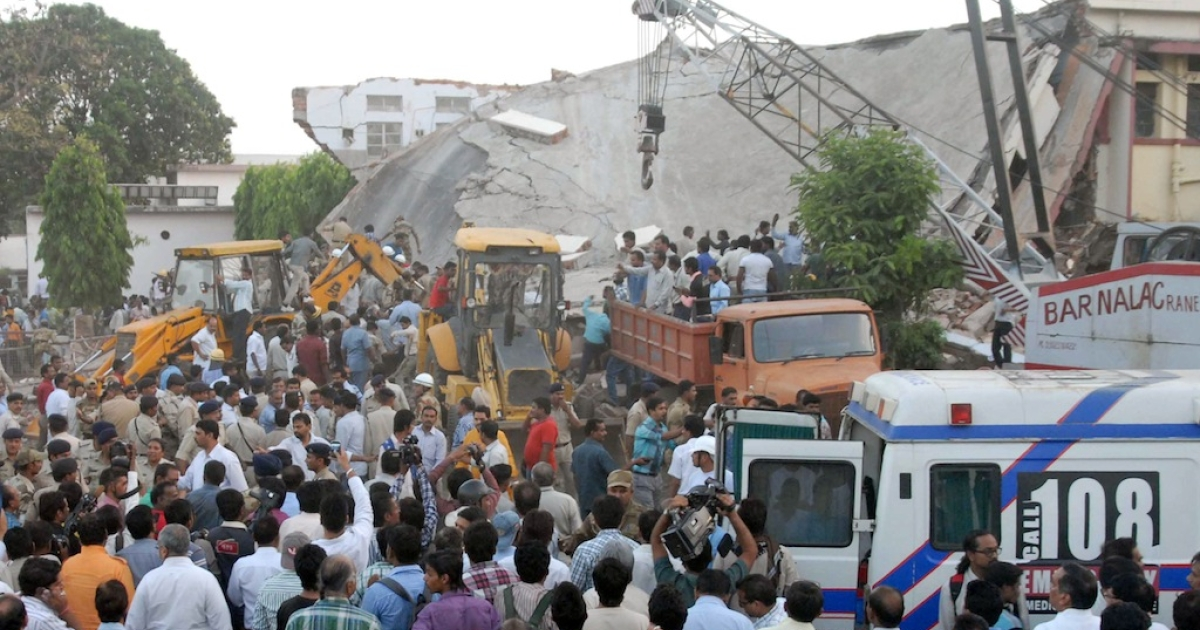 Onlookers and rescue personnel are pictured at the scene of a hospital collapse in Bhopal on April 26, 2013. Up to 15 people, mostly patients, were feared trapped after part of a hospital roof caved in on Friday in the central Indian city of Bhopal, officials and eyewitnesses said.</p>