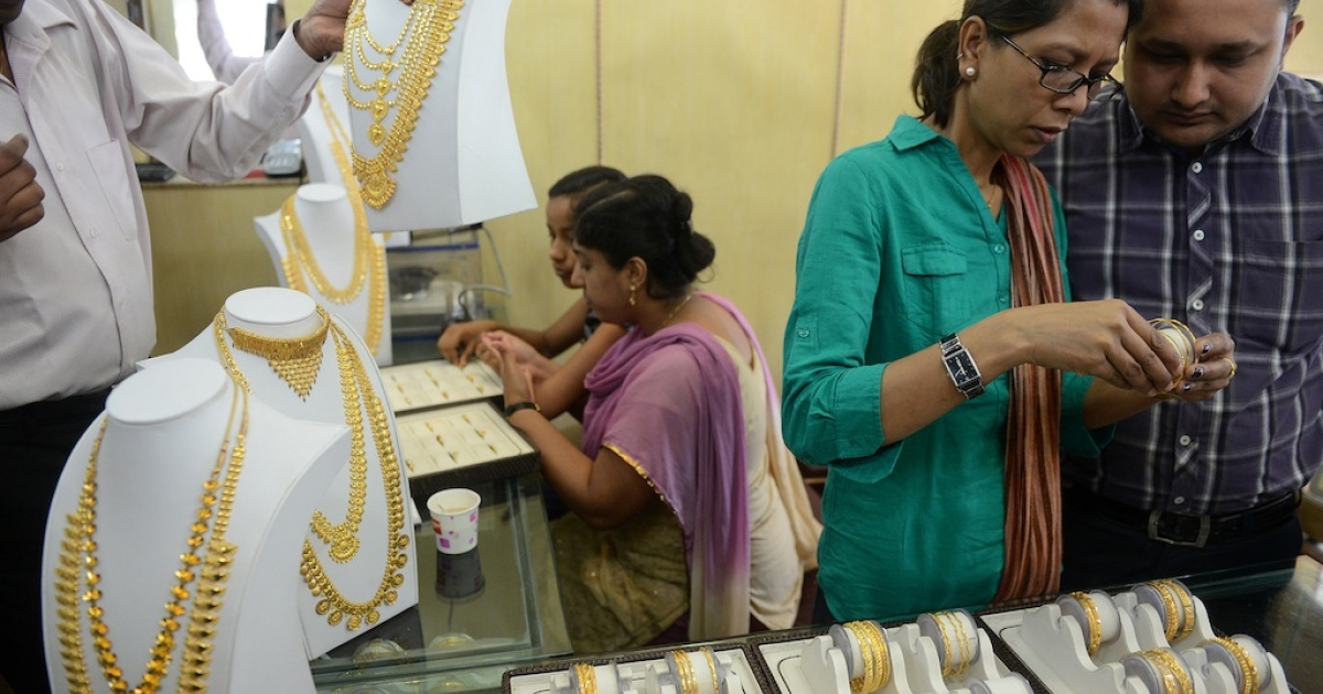 Indian customers buy gold jewelry at a shop in New Delhi on April 16, 2013.</p>