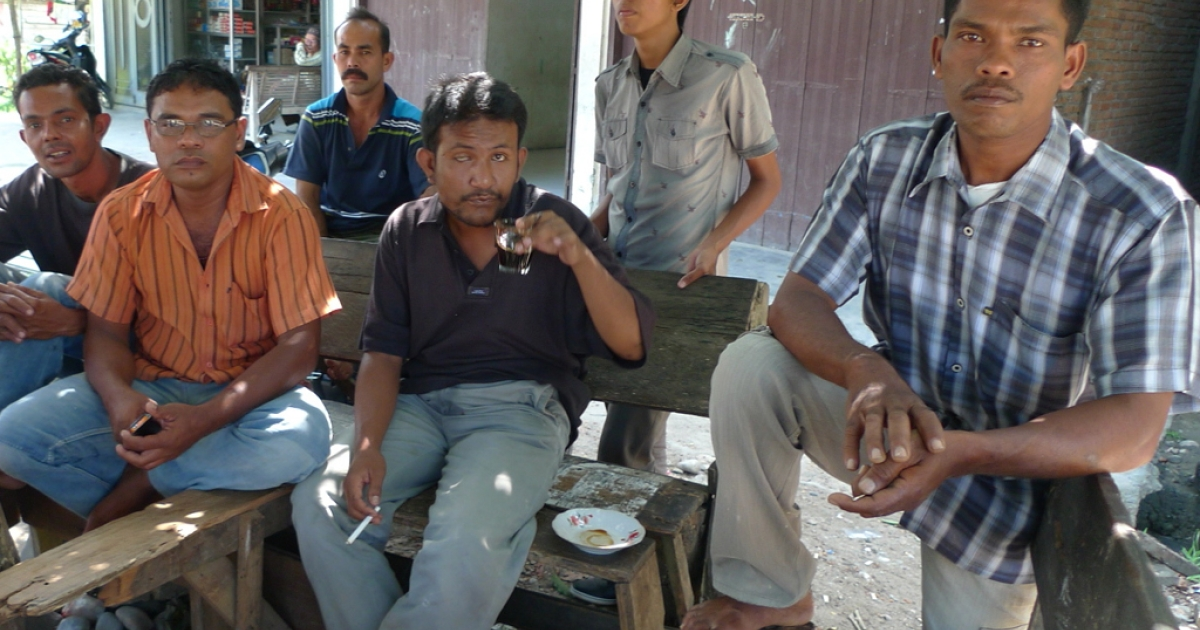 A group of men sit outside a claptrap coffee shop near ExxonMobil's facility in Lhokseumawe. Ibrahim Ismail, the man in orange, used to work as a contractor for the company. He says few of its profits have gone back to the community, particularly as production has slowed.</p>
