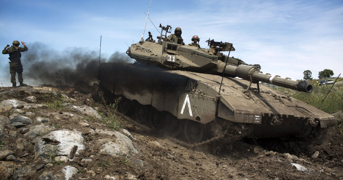 An Israeli Merkava tank maneuvers during a drill in the Israeli annexed Golan Heights near the border with Syria on April 24 2013. Israel's Brigadier General Itai Brun, head of research and analysis in the army's military intelligence division, said that the Damascus regime was guilty of using chemical weapons against rebel fighters.</p>
