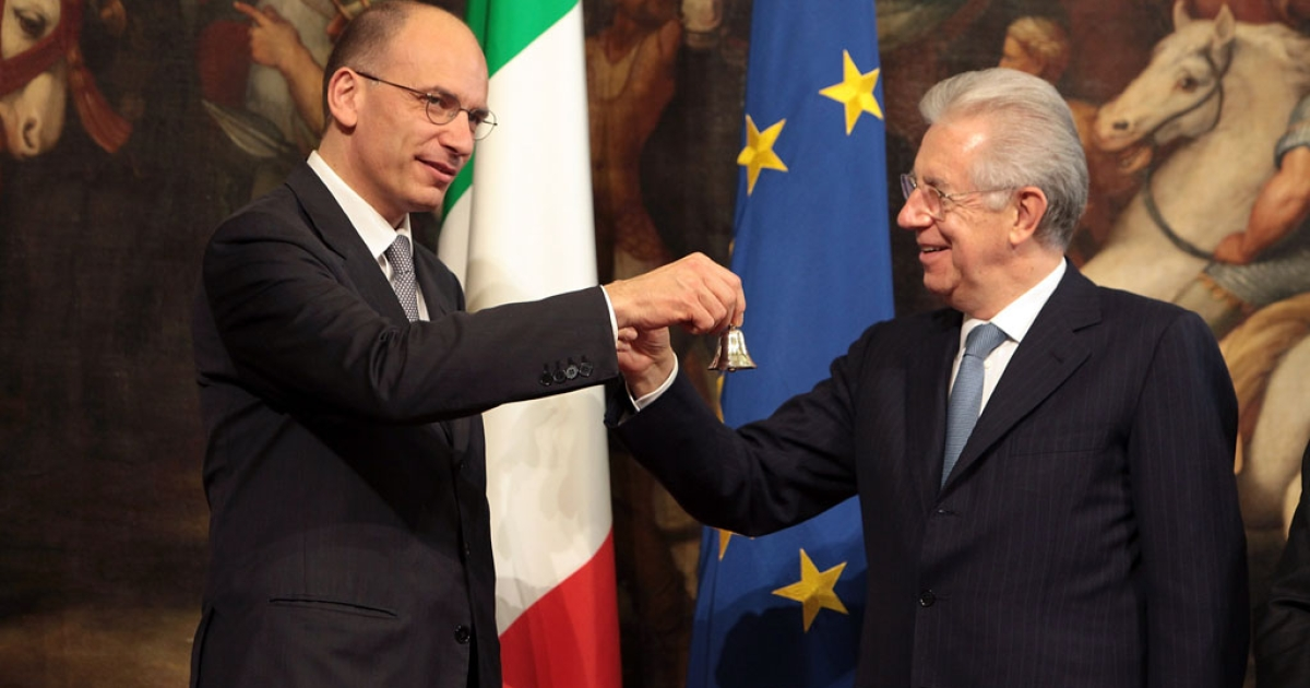 Italy's new Prime Minister Enrico Letta (L) rings the bell which he received from outgoing Prime Minister Mario Monti (R) marking the moment he takes office of the Prime Ministry at Palazzo Chigi on April 28, 2013 in Rome, Italy. The new coalition government was formed through extensive cooperation agreements between the right and left coalitions after a two-month long post-election deadlock.</p>