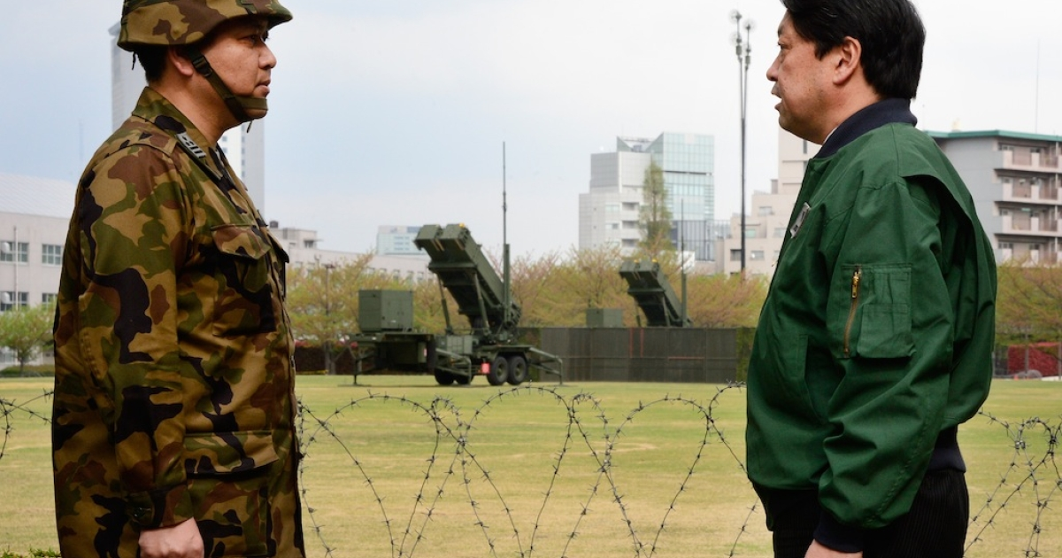 Japanese Defence Minister Itsunori Onodera (R) listens to a commander of Patriot Advanced Capability-3 (PAC-3) missile corps (L) at the Defence Ministry in Tokyo on April 10, 2013.</p>
