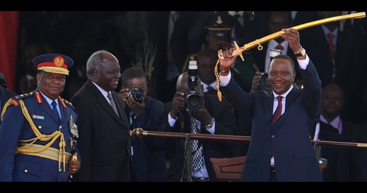 Kenya's 4th President Uhuru Kenyatta receives a symbolic sword of power from outgoing president Mwai Kibaki (2L) after he was sworn into office on April 9, 2013 in Nairobi. Uhuru Kenyatta was sworn in as Kenya's fourth president on Tuesday to thunderous cheers from tens of thousands of supporters, despite facing trial on charges of crimes against humanity.</p>