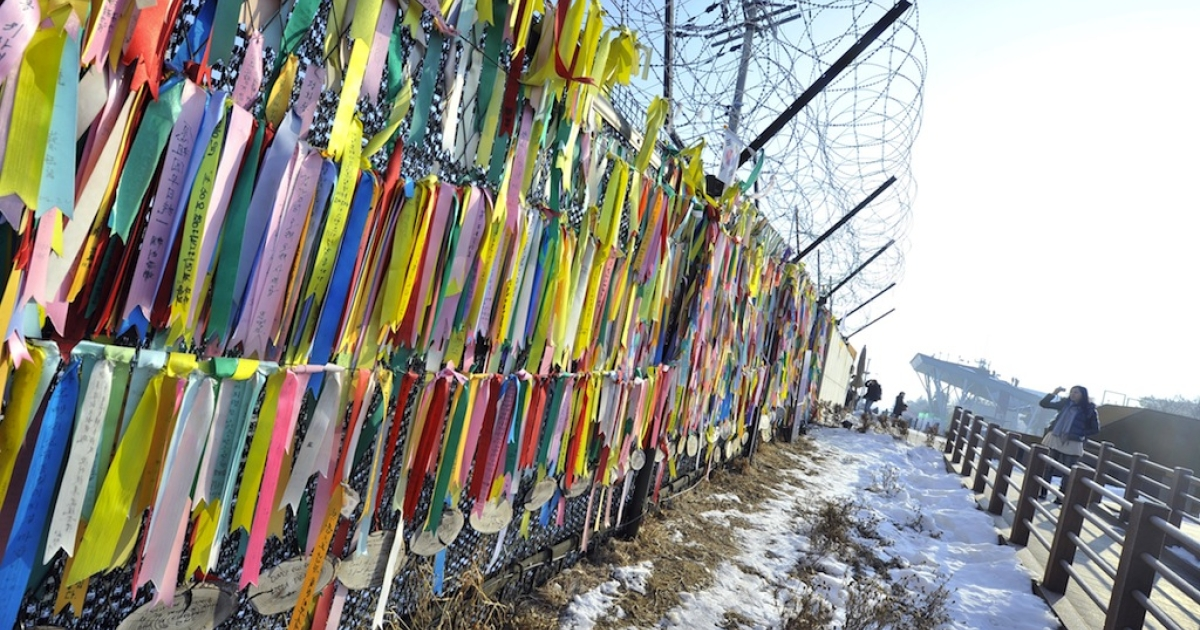 A visitor looks at 'reunification ribbons' displayed on a military iron fence at Imjingak peace park in Paju near the demilitarized zone dividing the two Koreas on Feb. 13, 2013.</p>