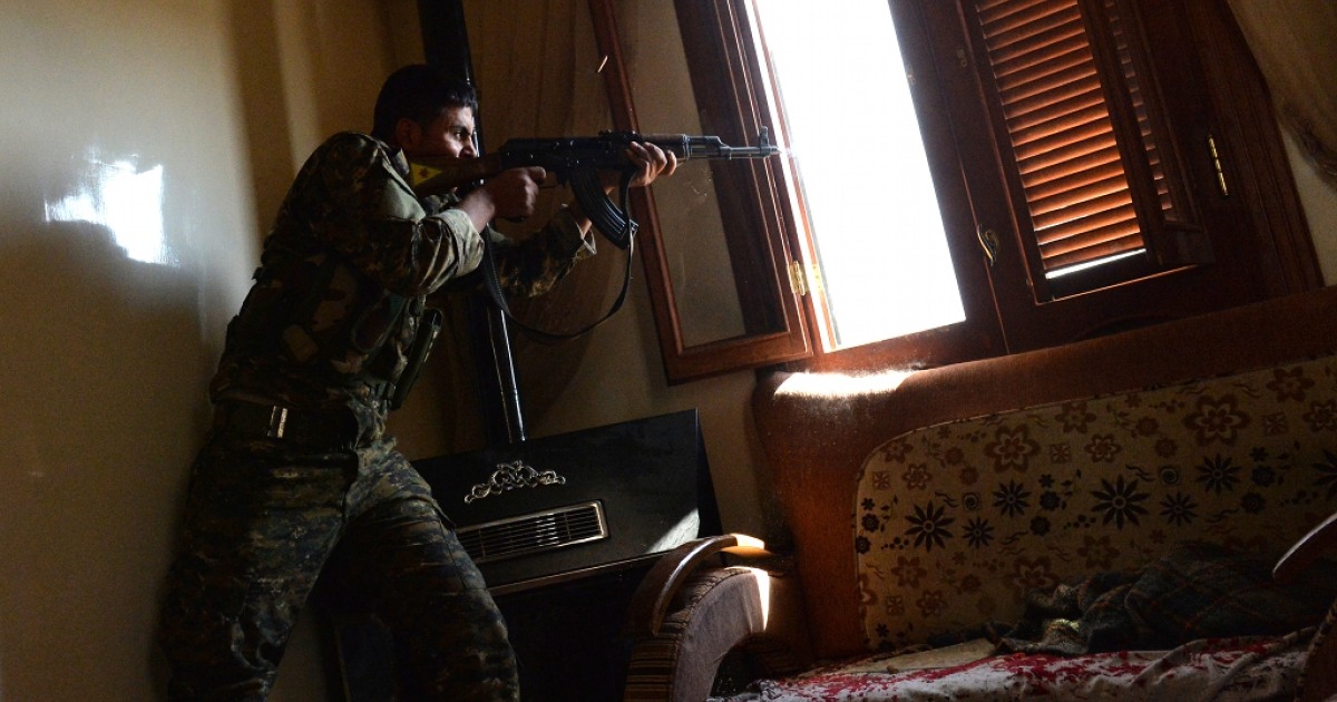 A Kurdish fighter from the Popular Protection Unit (YPG) fires towards Syrian government forces inside a building in the majority-Kurdish Sheikh Maqsud district of the northern Syrian city of Aleppo, on April 21, 2013.</p>