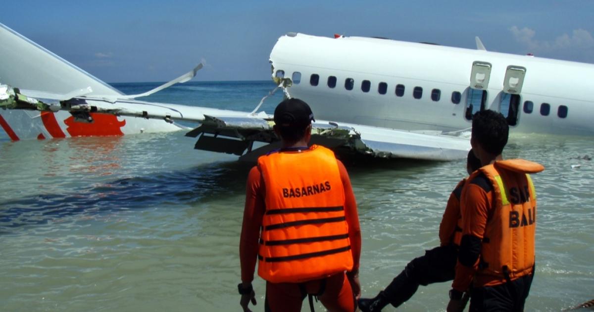 This handout photo released by the Indonesian Search And Rescue Agency (SAR) on April 14, 2013 shows workers looking at a Lion Air Boeing 737 lying submerged in the water after missing the runaway during landing at Bali's international airport near Denpasar.</p>